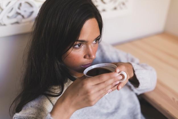 Primo piano di una ragazza adolescente che beve caffè dalla tazza