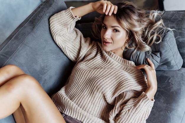 Primo piano di una ragazza bionda moderna in un maglione sdraiato sul divano