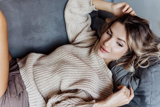 Primo piano di una ragazza bionda moderna in un maglione
