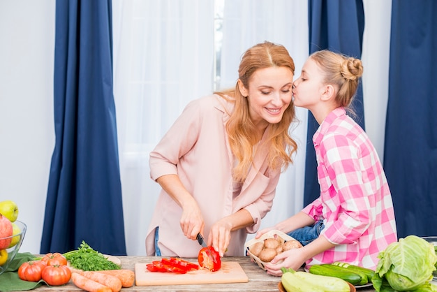 Primo piano di una ragazza che bacia sua madre che taglia le verdure con il coltello nella cucina