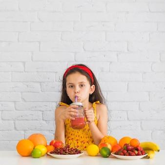 Primo piano di una ragazza che beve frullati di fragole