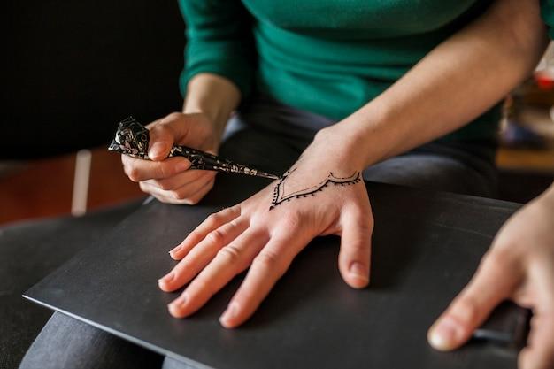 Primo piano di una ragazza che disegna heena sulla mano della femmina