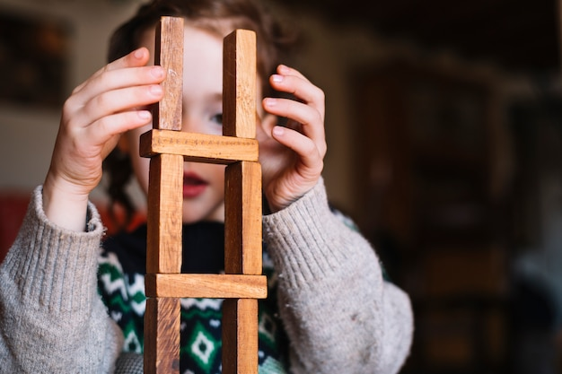 Primo piano di una ragazza che equilibra i blocchi di legno impilati
