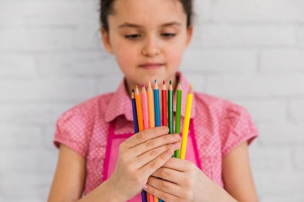 Primo piano di una ragazza che esamina le matite multicolori che si levano in piedi contro la parete bianca