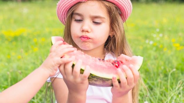 Primo piano di una ragazza che mangia anguria nel parco