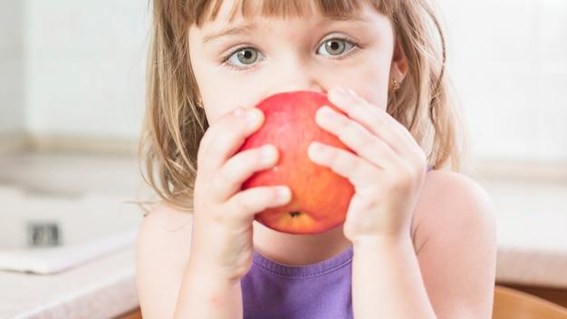 Primo piano di una ragazza che mangia mela rossa matura