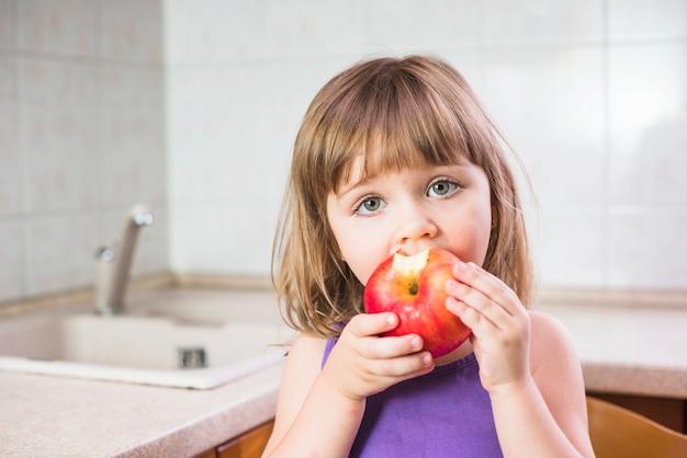 Primo piano di una ragazza che mangia mela rossa sana