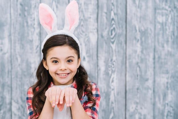 Primo piano di una ragazza che posa come coniglietto contro fondo grigio di legno