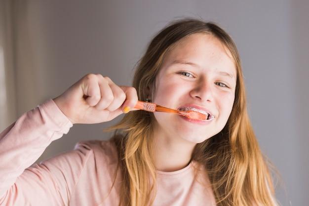 Primo piano di una ragazza che pulisce i denti con lo spazzolino da denti