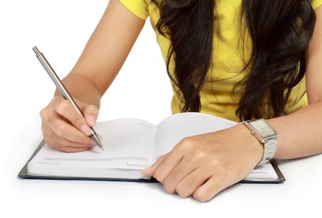 Primo piano di una ragazza che scrive in un taccuino