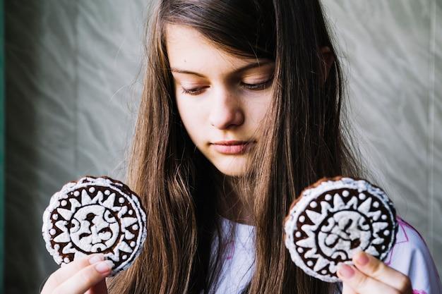 Primo piano di una ragazza che tiene due biscotti di glassa al forno