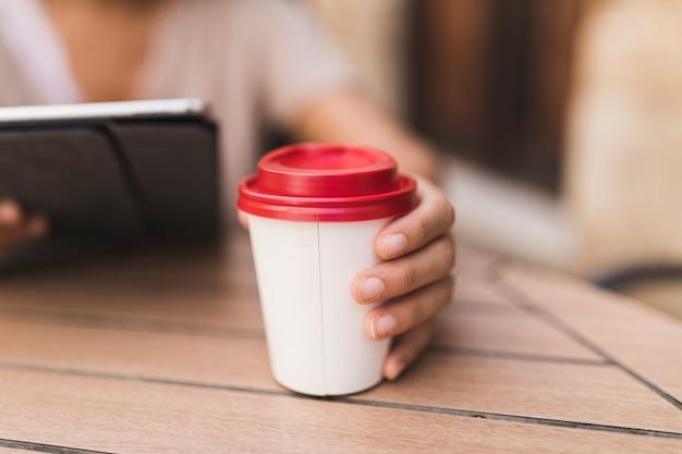 Primo piano di una ragazza che tiene tazza di caffè da asporto sul tavolo