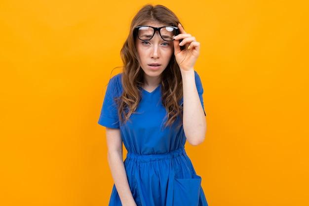 Primo piano di una ragazza con gli occhiali con gli occhi chiusi su uno sfondo giallo studio