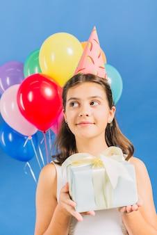 Primo piano di una ragazza con il regalo di compleanno davanti a palloncini colorati