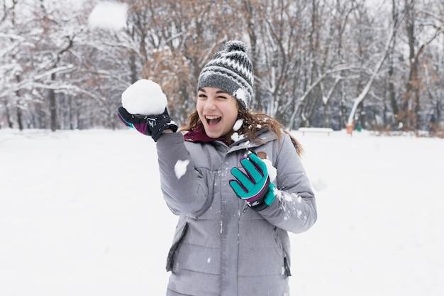 Primo piano di una ragazza felice che gioca con la neve nella foresta