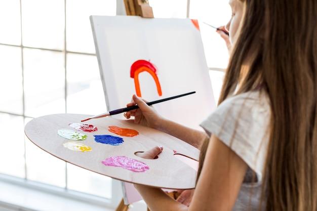 Primo piano di una ragazza in piedi davanti a tela mescolando la vernice rossa con pennello