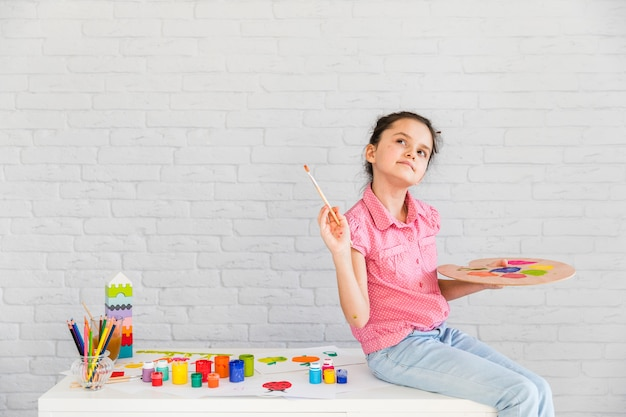 Primo piano di una ragazza premurosa che si siede sul tavolo bianco tenendo il pennello e la tavolozza