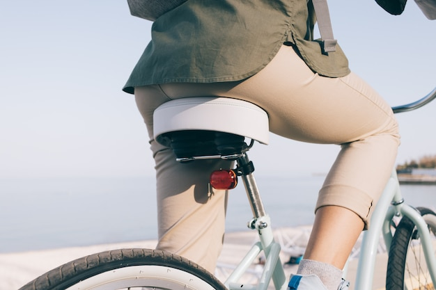 Primo piano di una ragazza snella in pantaloni beige e una camicia verde che si siede su una bici da spiaggia contro il mare