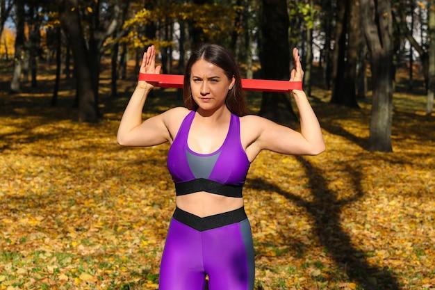 Primo piano di una ragazza sportiva facendo esercizi con un elastico di fitness nel parco