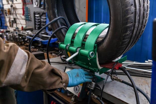 Primo piano di una ruota di automobile, una gomma è in piedi su una macchina equilibratrice per bilanciamento in un'officina automobilistica.
