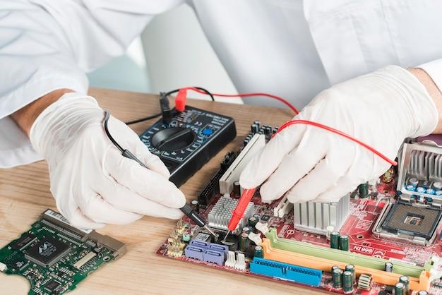 Primo piano di una scheda madre d'esame della mano maschio del tecnico con il multimetro digitale