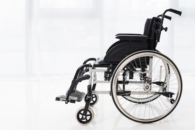 Primo piano di una sedia a rotelle vuota in una stanza con la tenda bianca