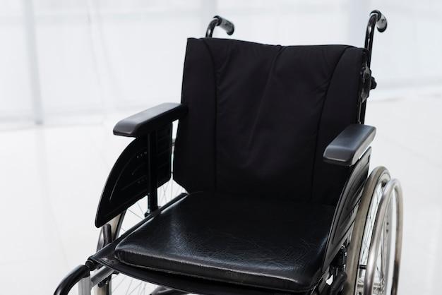 Primo piano di una sedia a rotelle vuota in una stanza