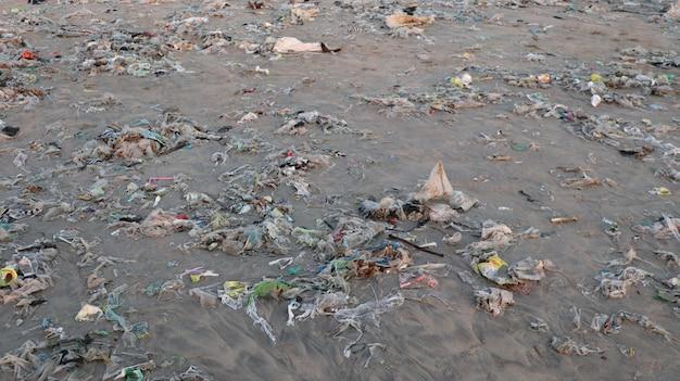Primo piano di una spiaggia di bea \ ch inondata di immondizia