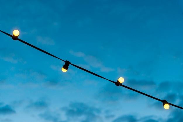 Primo piano di una stringa di luci con cielo blu