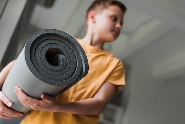 Primo piano di una stuoia di esercizio grigia di rotolamento della tenuta del ragazzo che distoglie lo sguardo