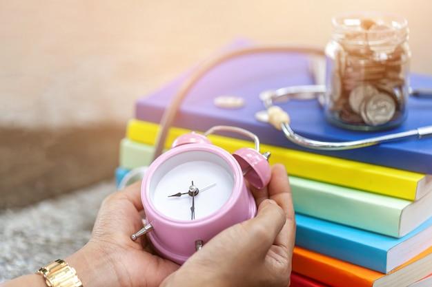 Primo piano di una sveglia rosa vintage nelle mani di una donna.
