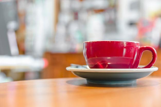 Primo piano di una tazza di caffè rossa sullo scrittorio di legno