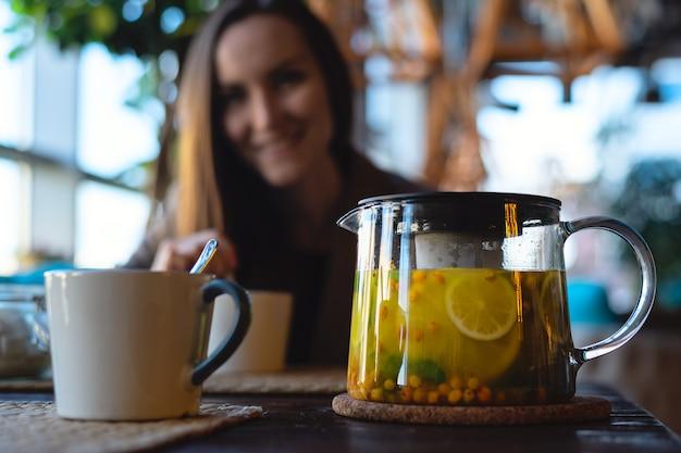 Primo piano di una tazza e una teiera di vetro con il tè dell'olivello spinoso con il limone e le erbe