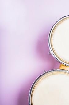 Primo piano di una vista elevata del tamburo di bongo su sfondo viola