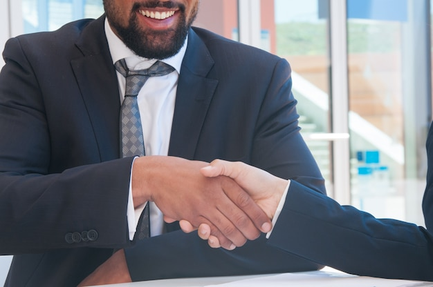 Primo piano di uomini d'affari si stringono la mano nel caffè all'aperto
