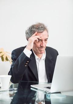 Primo piano di uomo anziano contemplato guardando portatile