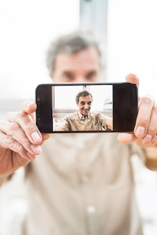 Primo piano di uomo anziano offuscato prendendo selfie con smartphone