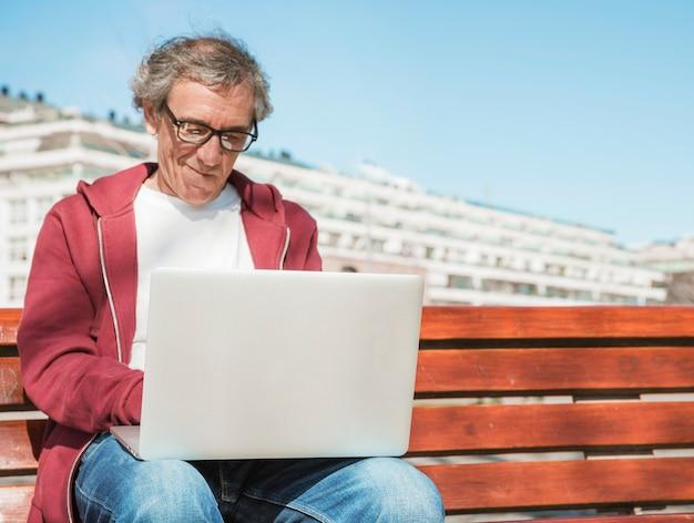 Primo piano di uomo anziano seduto sulla panchina utilizzando il computer portatile