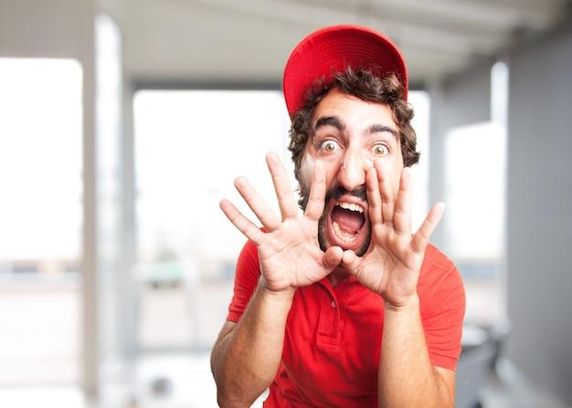 Primo piano di uomo arrabbiato con tappo rosso grida