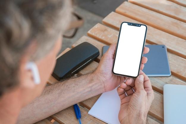 Primo piano di uomo che guarda cellulare con schermo bianco vuoto