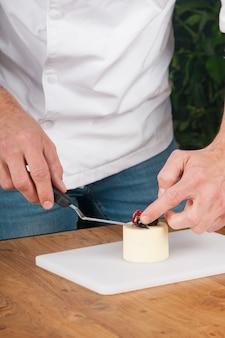 Primo piano di uomo che mette bacche sulla pace di gelato al tavolo