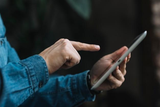 Primo piano di uomo che punta il dito sulla tavoletta digitale