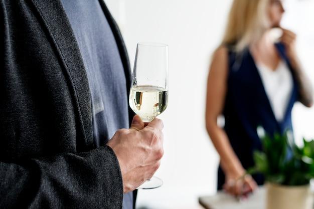 Primo piano di uomo che tiene il bicchiere di vino bianco
