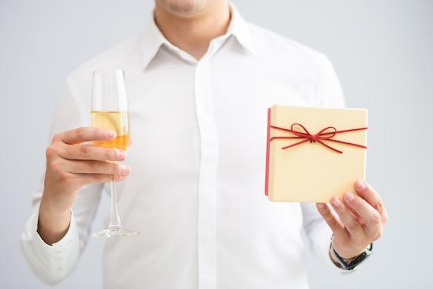 Primo piano di uomo che tiene in vetro con scatola regalo e champagne