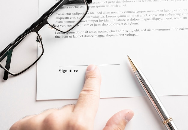 Primo piano di uomo d'affari che punta alla riga della firma nel contratto