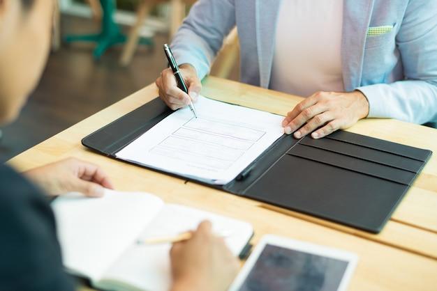 Primo piano di uomo d'affari che si siede al tavolo e compilando il documento