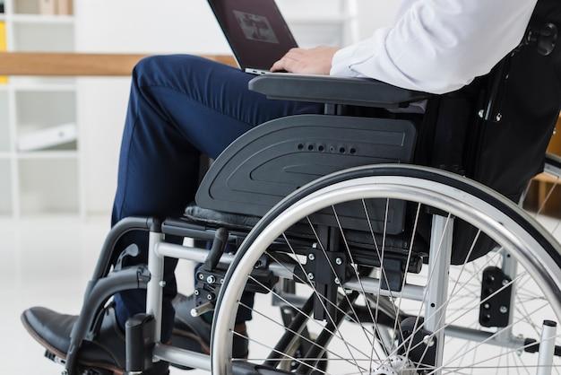 Primo piano di uomo d'affari che si siede sulla sedia a rotelle con laptop