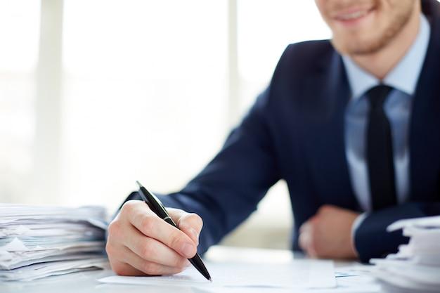 Primo piano di uomo d'affari che tiene una penna