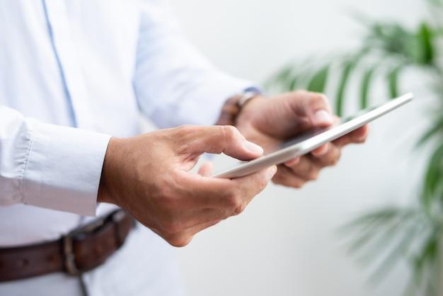 Primo piano di uomo d'affari navigando su tablet pc
