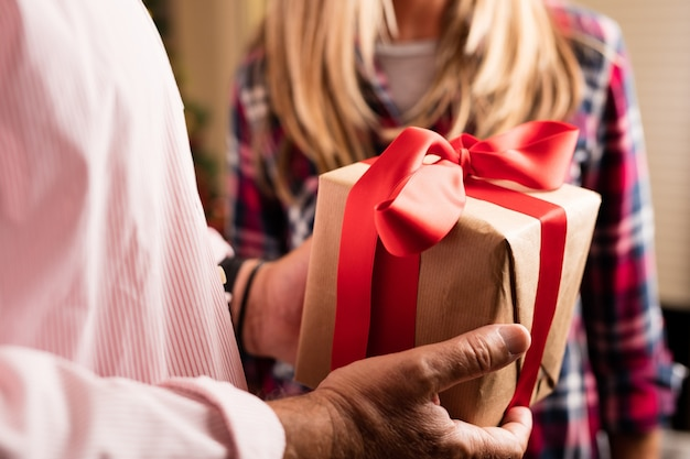 Primo piano di uomo in possesso di un regalo con fiocco rosso